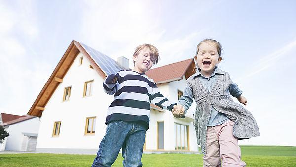 Kinderen spelen voor huis met zonnepanelen